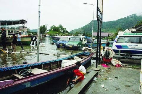 Bocah-bocah bermain di Dermaga Ajibata, Kabupaten Toba Samosir, Sumatera Utara, yang terendam akibat naiknya air danau, Rabu (10/12). Selain hujan, penyebab kenaikan air danau adalah kerusakan hutan seputar danau. Dari 260.154 hektar kawasan tangkapan air, seluas 116.424 hektar lahan kini kritis.